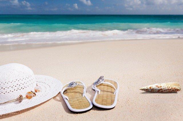 Una bella immagine di una spiaggia con il mare turchese e la sabbia bianchissima. In primo piano ci sono un paio di ciabatte da mare e un cappello bianco a tesa larga